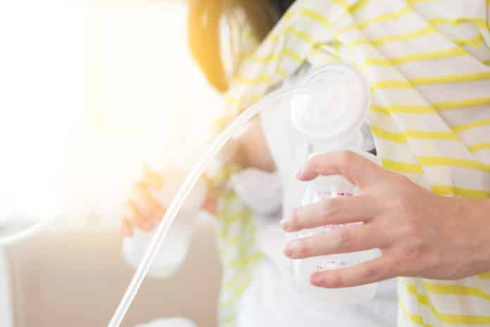 A woman expressing breast milk using a breast pump